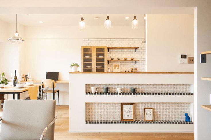 豊中市、築33年の中古マンションをフルリノベーション。 紺のリビング壁が、白を基調とした空間にアクセントを。 また、キッチンカウンター壁面の飾り棚や玄関、 トイレなどにタイルを、床にコルクをあしらうなど、 シンプルでありながらやわらかく、あたたかみのある空間に。