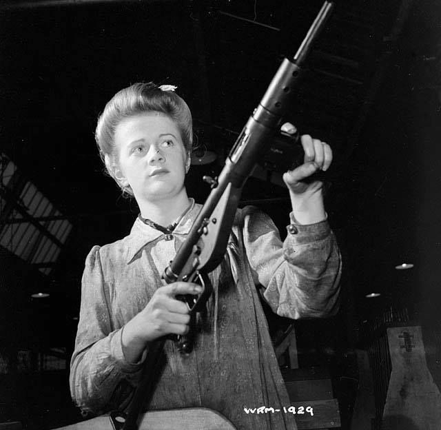 Factory worker posed with finished Sten sub-machinegun Small Arms Plant Long Branch Ontario Canada 26 May 1942.