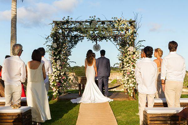 Cerimônia de casamento na praia em Trancoso - decoração do altar com estrutura de flores e luminárias no caminho