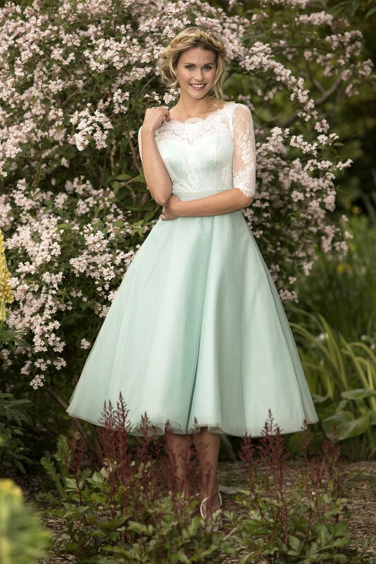 M648 - NEW COLLECTION IN STORES AUGUST 2015. Sassy tea length bridesmaid dress with a delicate sheer lace neckline and sleeve, pleated sash and full Fifties style tulle skirt. Zip up back with buttons and elasticated buttons with neat finish. Pictured here in Aqua with Ivory Lace