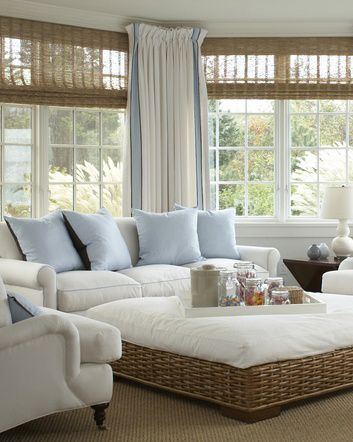 White is the primary color in this light and bright room, accented in pale blue.  The wicker ottoman, the natural blinds and plenty of windows gives it an airy feel.