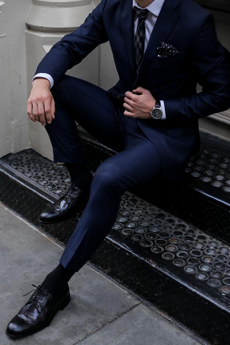 Dark navy suit + plaid tie + polka dot pocket square + black wingtip shoes