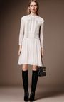 Rendered in delicate silk crepon, this **Burberry** dress features a jewel neck with sheer bracelet length sleeves, a relaxed bodice with pleated luggage stitching details throughout, and a drop waist skirt with a knee length hem.