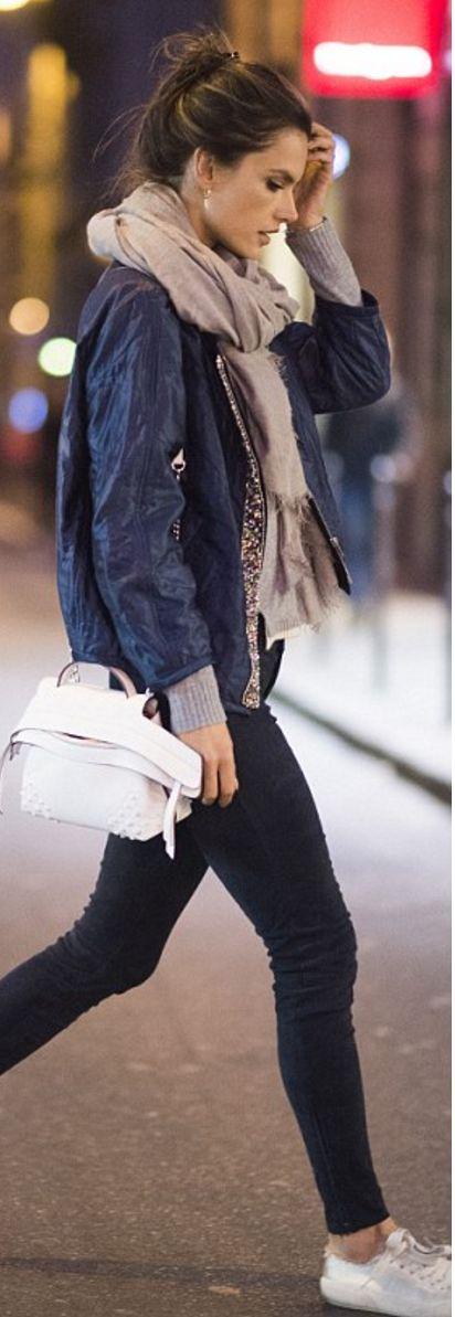 Who made  Alessandra Ambrosio's sneakers, blue skinny pants, jacket, and white studded handbag?