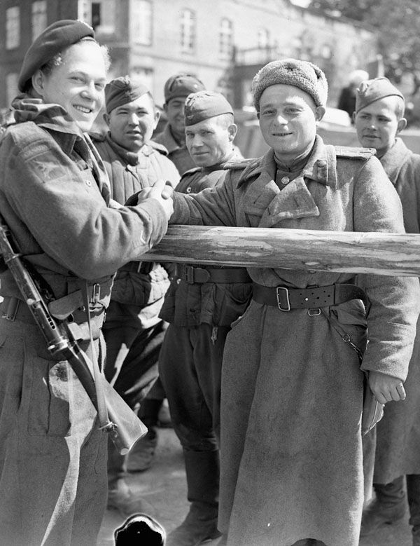 Canadian shaking hands with a Russian soldier, Wismar, Germany, 4 May 1945. Photographer: Richer, Charles H. MIKAN 3210996