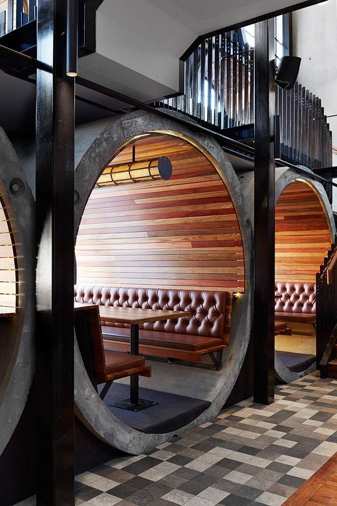 The Prahran Hotel in Melbourne by Techne Architects. The use of concrete pipes to allow views in and out, creates enclosed booths with upholstered leather seats, recycled gum slats and acoustic absorption mats