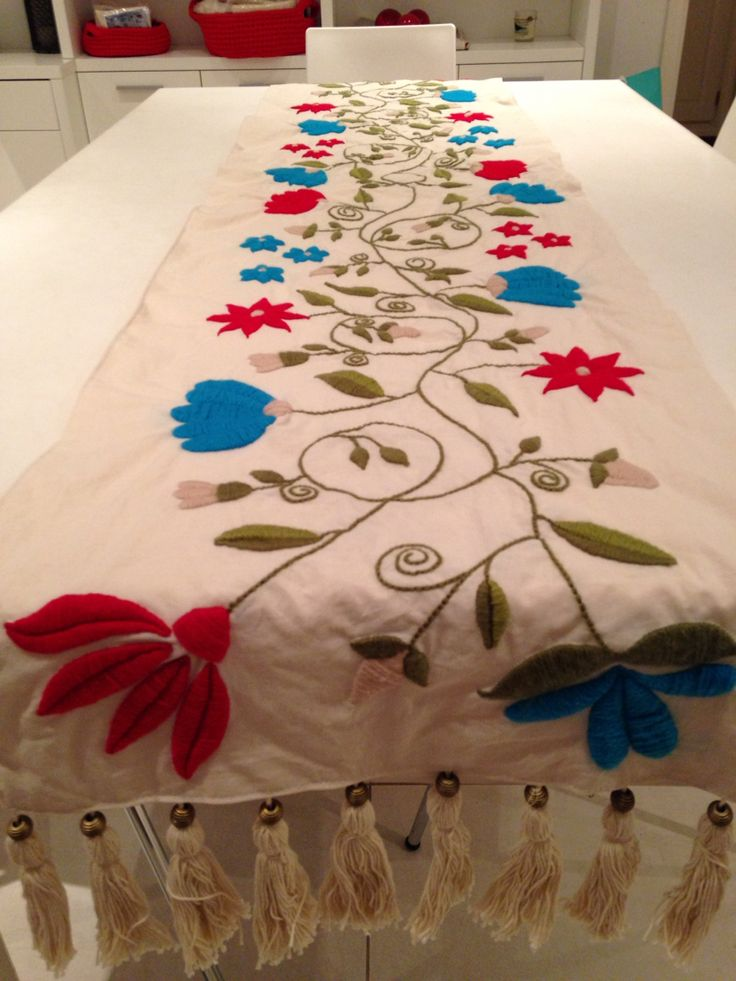 Camino de mesa, bordado a mano con lana, con detalle de borlas de hilo de algodon, en sus extremos