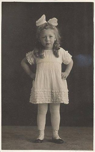 Vintage photograph of a little girl wearing all white with ruffles and hair bow.