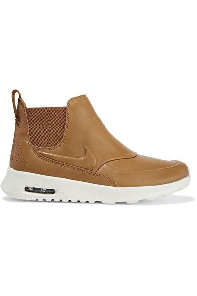 Nike's 'Thea' sneakers are updated this season in a sleek and modern silhouette. This tan pair is designed with a visible Air Unit and lightweight foam midsole for cushioning, and has elasticated sides to ensure they slip on and off with ease. The rubber waffle sole provides traction on inclement days.