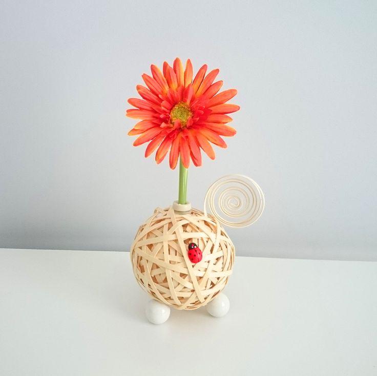 Centro Floral Aromático Flowerfresh modelo Ball. Bola central de color verde hecha de tiras de ratán. Cuenta con complementos como espiral y mariquita de madera. Además puedes elegir el aroma a evaporar.