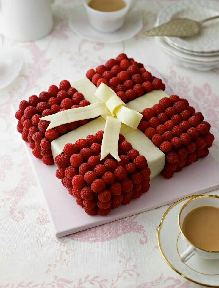 Raspberries and a white fondant bow cake