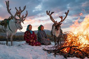 Purev and Buyantogtokh, two members of a Tsaatan family, sit near a fire in the Altai mountains. Tsaatans are a nomadic community who herd reindeer year-round