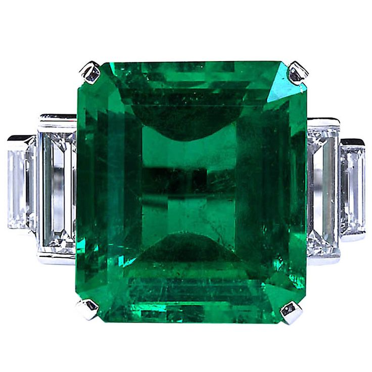 A large exceptional color 16.68 carat emerald cut natural Colombian emerald set in a platinum ring with four diamond baguette shape side stones in D color IF clarity weighing 3.55 carats total. Emerald dimensions: 18.04 x 15.68 x 8.10mm, c. 2010