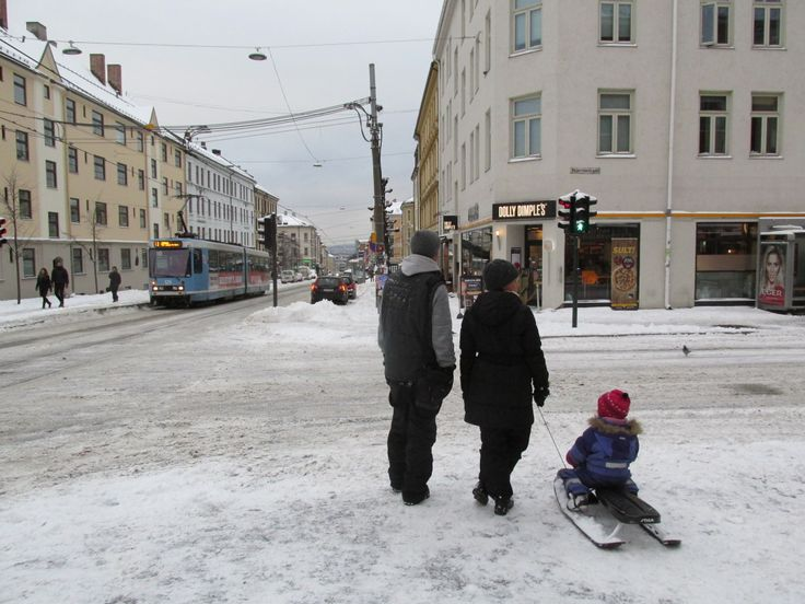 THE SNOW ARRIVED OSLO YESTERDAY: December 8. 2013. A kid is sliding on the pavement with parents outside my local café Kaffegutta at Torshov - Oslo.