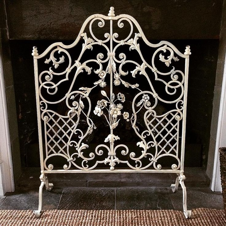 An ornate wrought iron fireplace screen adds visual interest to this simple  hearth   fireplacescreensBest 25  Wrought iron fireplace screen ideas on Pinterest  . Metal Fireplace Screens. Home Design Ideas