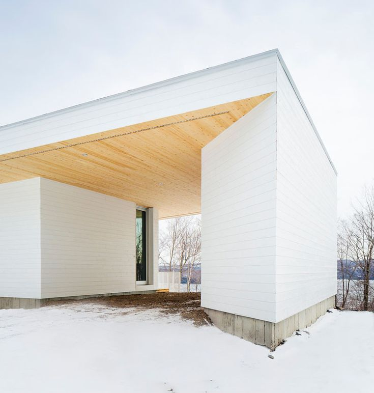 The white painted wood siding of this home in Quebec, is broken up by the light cedar wood on the roof soffits.