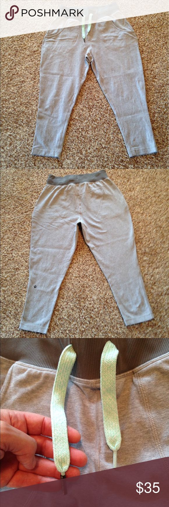 Lululemon pants Excellent used condition. Crop length Lululemon pant. Two front pockets. Drawstring waist. One of the metal wraps came of the one string shown in one of the photos. Light gray with a dark gray waistband. Pretty light green/blue drawstring. lululemon athletica Pants Ankle & Cropped