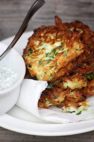 ZUCCHINI FRITTERS w/ DILL TZATZIKI  1 lb zucchini, coarsely grated  1 t sea salt and more to season  5 garlic cloves, crushed through a press  2-4 T finely chopped fresh dill, to taste  Freshly ground black pepper  1 cup Greek yogurt  Juice of 1/2 lemon to taste  1 cup ricotta cheese  2 large eggs  1/4 cup all-purpose flour  Small handful of fresh basil, chopped  Small handful of flat leaf parsley, chopped  Vegetable oil for frying