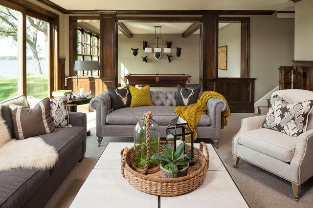 Martha O'Hara Interiors (OBSESSION!)  Pretty, neutral living room. Gray tufted chesterfield sofas. Mustard color throw and dark gray pillows. Tiled coffe table with woven basket tray, terrariums and lantern. Large sliding doors, craftsman style molding and beige walls.