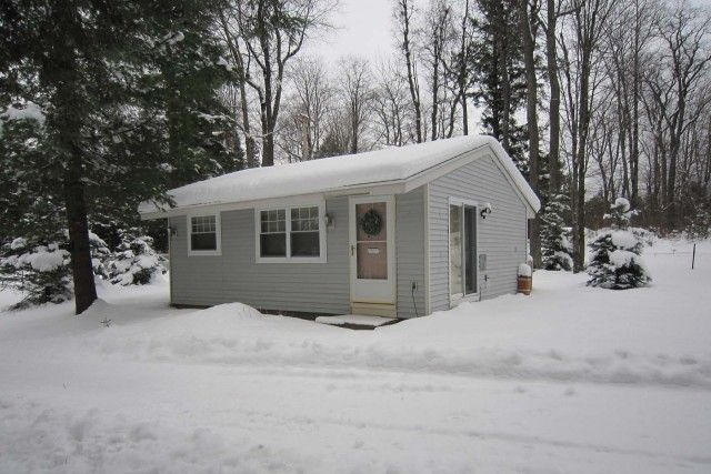 #5299 PRISTINE CONDITION – Low maintenance, year round and adjoins 10' sandy lake access to Otter Lake. Living/dining/kitchen with woodstove, 2 bedrooms & bath. Furnished, propane heat & ready for you to enjoy. Snowmobile trail access nearby. $135,000.