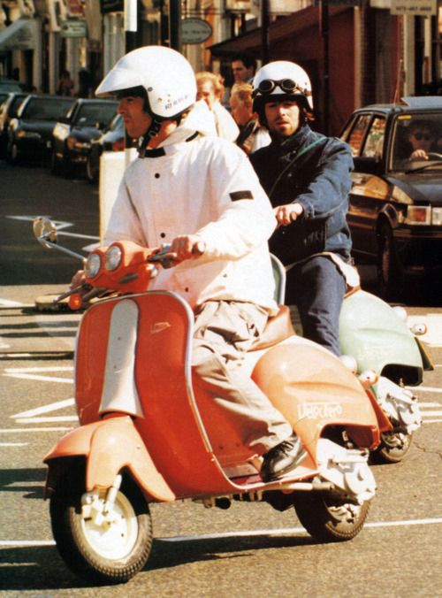 Liam and Noel riding scooters.   44 Photos That Will Transport You Back To The '90s