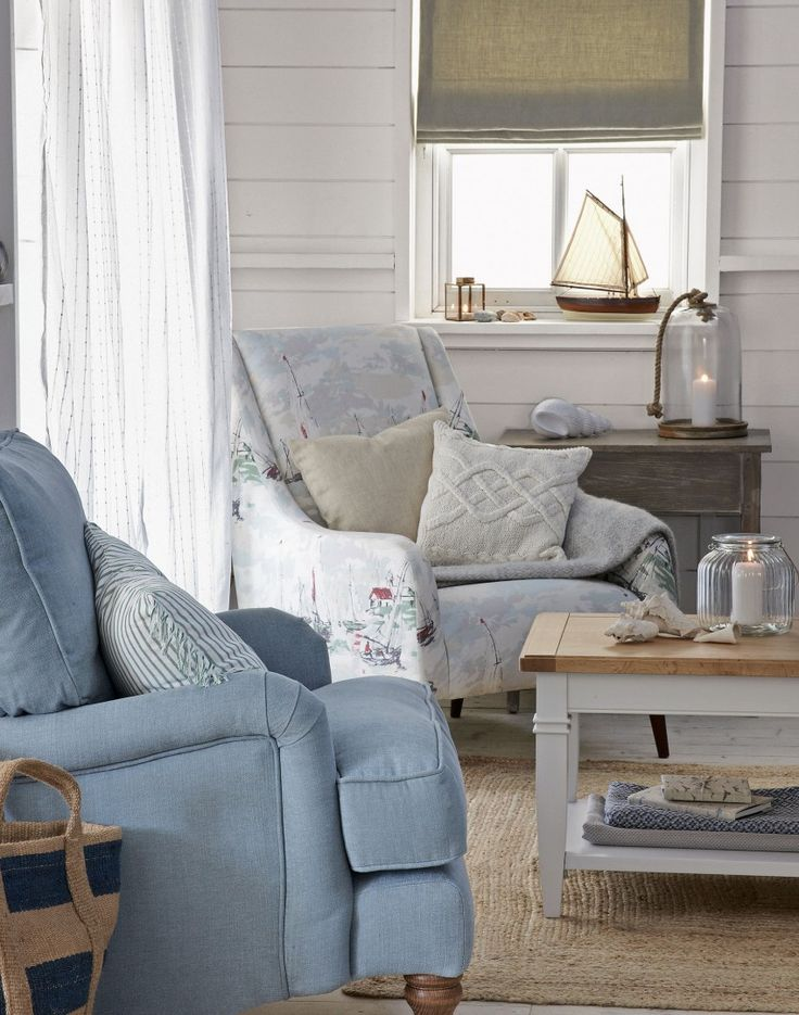 White washed walls and pale wooden floors form the backdrop to this effortlessly stylish look. Shore-inspired prints and faded linen fabrics adorn two inviting, classic armchairs offering the perfect spot to enjoy coastal living.