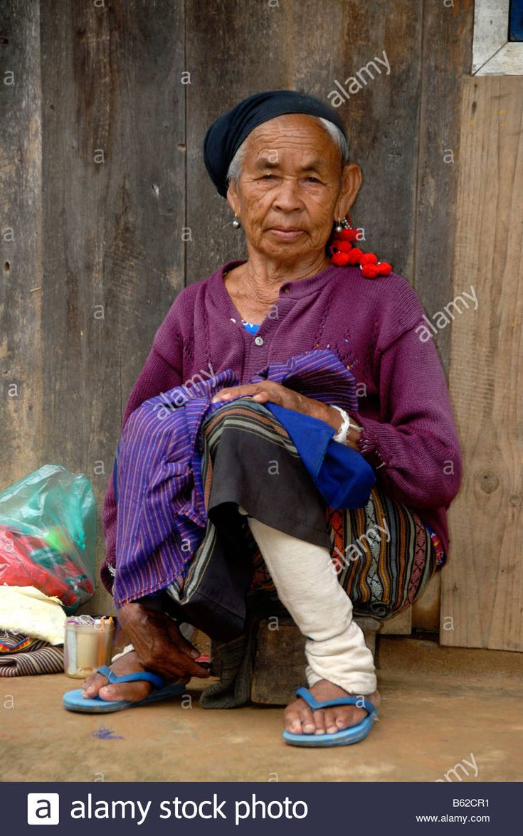 Old woman of the Phunoy tribe dressed in typical white leggings and headdress with red pompoms, Ban Thabak, Phongsali Province, Stock Photo