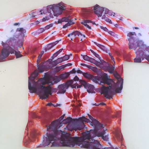 This is a vibrant hand-dyed t-shirt for kids reminiscent an all seeing eye! Use your imagination to find interesting images in the design. This one of a kind ice dyed item is unique and a great gift for one of the young ones in your life! Colour- Red, Purple, White Size- Large Youth (14-16) Brand- M&O Youth  To create this artistic design ice is used to deposit professional quality dye onto the fabric and the abstract art is created over a period of 24 hours. This item has been pre-shrunk…