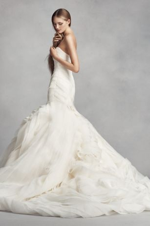 The dramatic skirt of this White by Vera Wang trumpet wedding dress is handcrafted with over 70 yards of bias-cut organza tiers. Two romantic rosettes complete this classic silhouette. White by Vera Wang, exclusively at David's Bridal Petite Polyester Chapel train Back zipper; fully lined Dry clean Imported Also available in regular and extra length