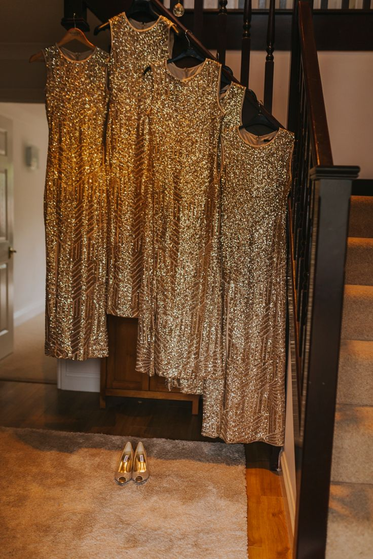 And all that glitters... The bridesmaid dresses hang patiently in the hallway, framing the bride's golden peep toe shoes. Photo by Benjamin Stuart Photography #weddingphotography #bridesmaids #goldtheme #goldwedding #golddress #weddingday #weddingshoes