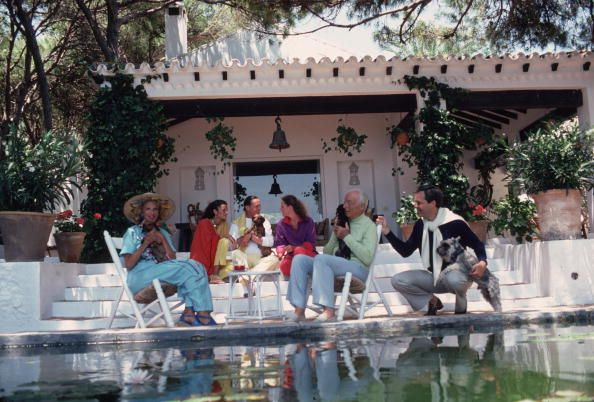 Title:Rothschild Home   Caption:August 1980: The Rothschild family round the pool at their home the villa Santa Margarita reputed to be the most beautiful house in Marbella. From l to r: Marie-Helene de Rothschild, Olympia de Rothschild, Baron Alexis de Rede (holding dog), Madam Hu       Artist:Slim Aarons  Date:1980