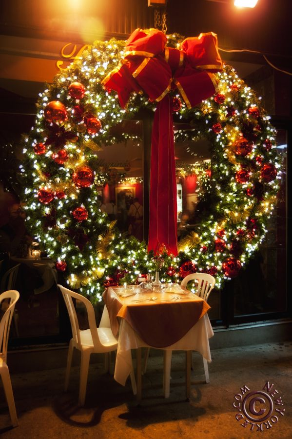 a spectacular christmas wreath adorns a glass wall in a restaurant somewhere looks like maybe pellegrinos in nyc winterchristmas pinterest