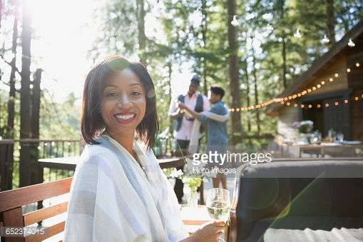 Stock Photo : Portrait smiling woman drinking wine at party on cabin balcony in sunny woods