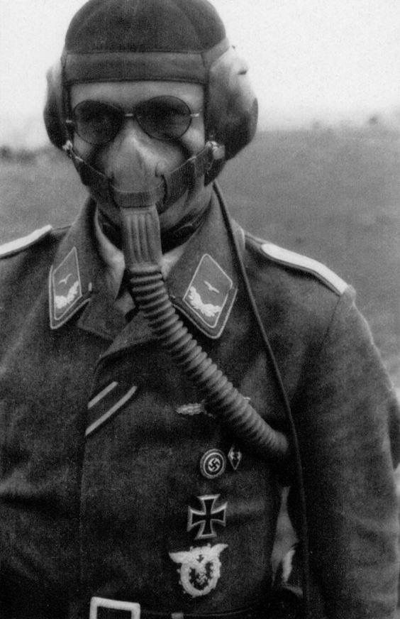 A rare photograph showing a German ace of the Luftwaffe wearing an oxygen mask along with varying war decorations including an iron cross 2nd class, a Luftwaffe flying clasp, a pilots observation badge, and two political pins: an NSDAP membership pin and a Hitler Youth pin. It was rather uncommon to see a member of any military branch except the Waffen-SS to adorn political decorations as one's loyalty is to lie solely towards the military, not an outside organization.
