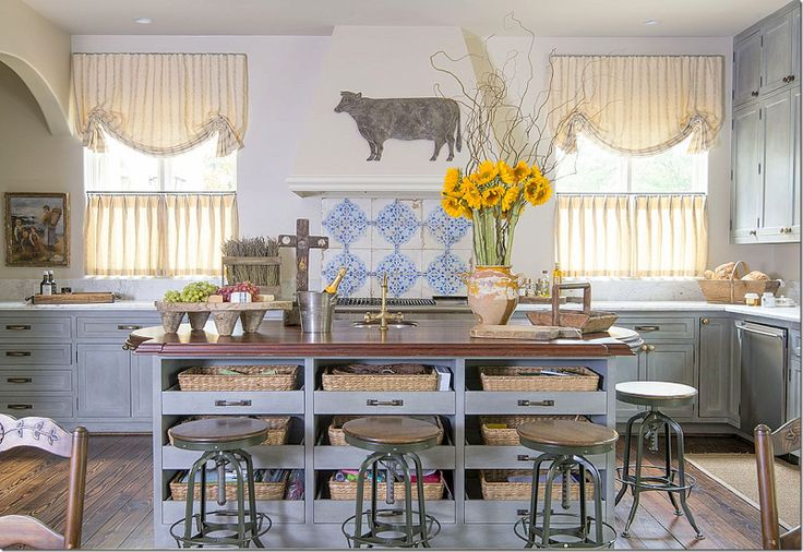 Great industrial stools around the island.  Cute window treatments in yellow stripes along with French styled accessories.  Love the painted cabinets and tiled backsplash mixed with the white marble.