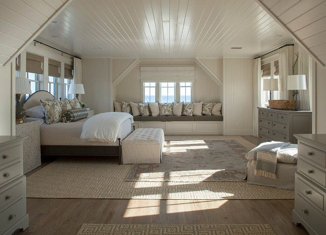 Gorgeous and spacious master bedroom in the attic with built-in day bed, grey furniture and hardwood flooring.