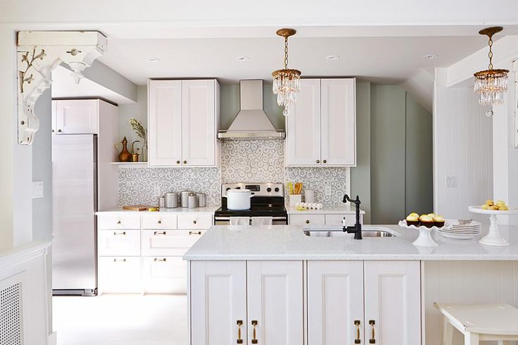 """White kitchen with a breakfast bar by Sarah Richardson for HGTV's """"Real Potential"""" (via Globe & Mail.)."""