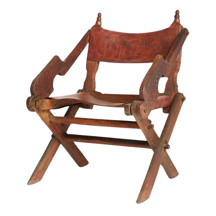 A one-of-a-kind piece from 1930s Mexico, this rustic chair steals the show. The backrest and seat are made from a reddish brown, hand-crafted leather that shows the strokes, texture and personal touch of its fabrication. Beautifully carved armrests create organic shapes of movement, with a crosshatched pattern carved into both sides. From top to bottom, there are beautiful details adorning the frame of this chair, from the scissored base up to the ornamental finials above.   In great vintage…