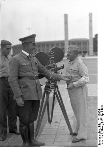Berlin.- Filmteam der Fox' Tönende Wochenschau mit Ausrüstung vor dem Olympia-Stadion in Vorbereitung auf die Sommerolympiade, Kameramann mit Filmkamera.