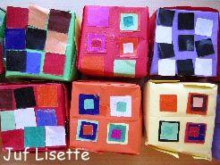 doos. Met zestien vierkantjes een doosje vouwen. Twee keer (boven- en onderkant). Versieren met plakvierkantjes.