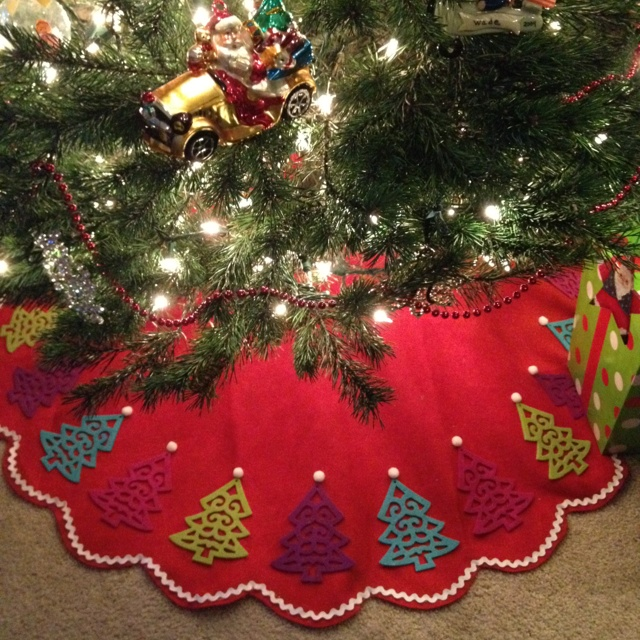 """Tree skirts are expensive!  I found a basic red scalloped felt tree skirt at Target for $5.  Then, I embellished it with """"felt tree ornaments"""" (also from Target), ric-rac, and white pom-poms.  New sewing...it took 15 minutes...and cost about $18!!!"""