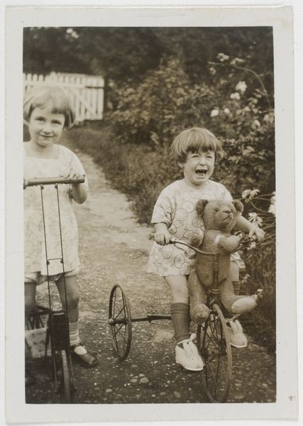 Author Elizabeth Jolley and (younger) sister Madelaine Winifred in the garden, 1927.  Monica Elizabeth Jolley AO (4 June 1923–13 February 2007) was an English-born award-winning writer who settled in Western Australia in the late 1950s.  Find more detailed information about this photograph: http://acms.sl.nsw.gov.au/item/itemDetailPaged.aspx?itemID=82004  From the collection of the State Library of New South Wales www.sl.nsw.gov.au