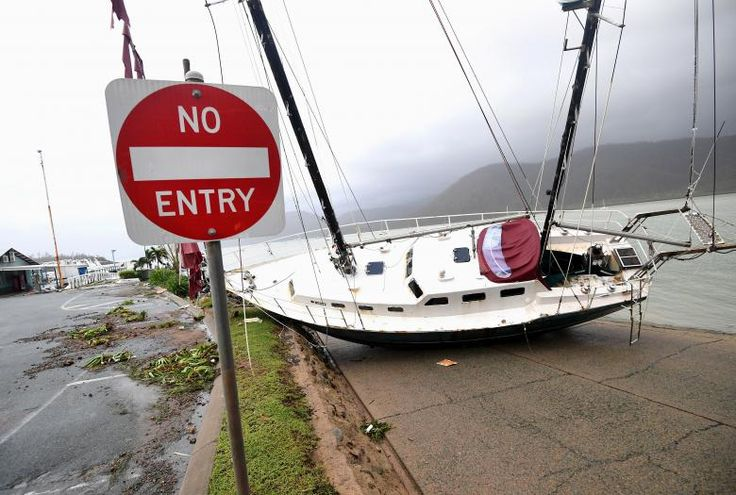 A boat is seen smashed against the bank at Shute Harbour, Airlie Beach. AAP/Dan Peled/via REUTERS