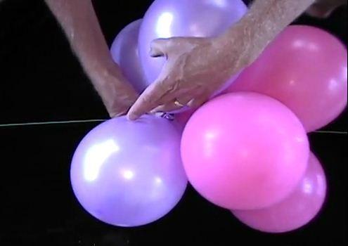Zelf ballonnenboog maken - de geknoopte ballonnen aan de draad of PVC-buis doe je op dezelfde manier: draai twee ballonnen rond de gemaakte knoop waarna de ballonnen vast zullen zitten