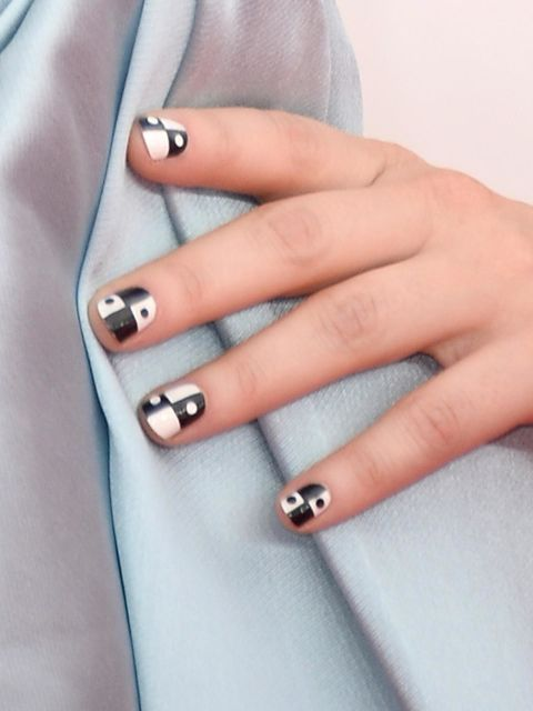 Zooey Deschanel's retro-inspired tips are easier to recreate than you think! After you paint your nails white, use a striker brush to draw a plus sign in black, then fill in two of the boxes. Then, dot black polka dots in the white squares and apply a topcoat!
