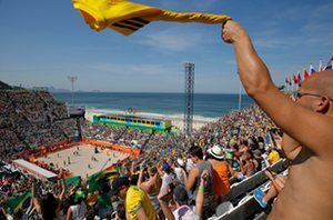 Fans celebrate as the Brazilian men's team win their opening beach volleyball match against Canada on Copacabana beach on day one of the 2016 Olympics in Rio de Janeiro