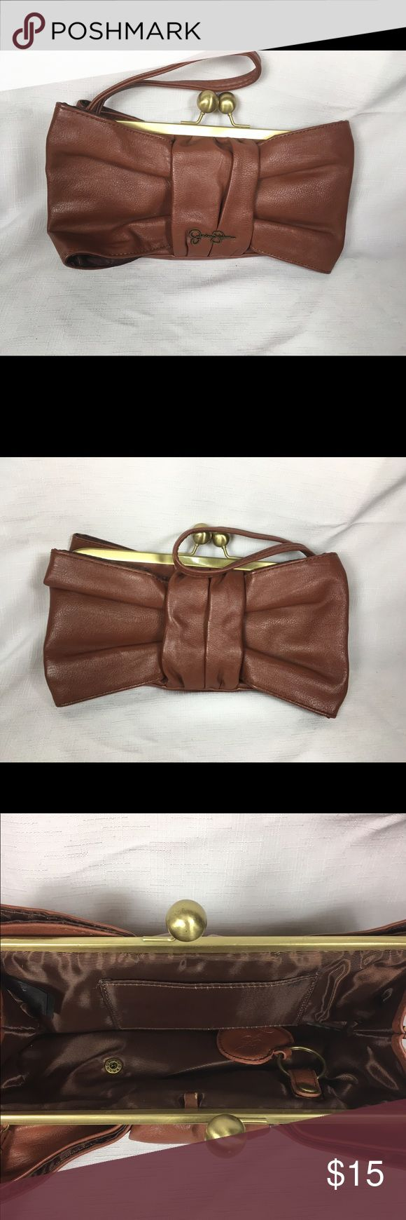 Jessica Simpson Brown Bow Clutch Adorable brown bow clutch/wristlet by Jessica Simpson.  Bag has an antiquey gold clasp detail. The inside is very clean. The little loop on the inside for your keys does have a little wear.  There also looks to be a small stain on the inside pocket.                                               Bag is roughly 11in x6in.    Bag is large enough for going out or when you just don't want to carry your big purse. Jessica Simpson Bags Clutches & Wristlets