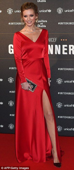 Making a statement: The Countdown presenter looked incredible in a bright red silk dress featuring a sexy thigh-high split as she arrived at Old Trafford on Wednesday night