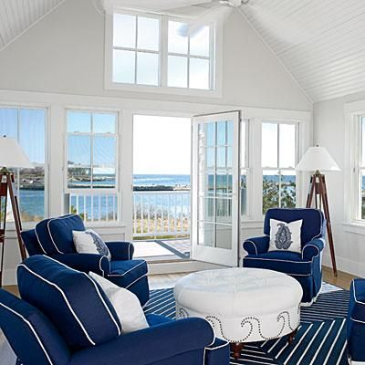Navy blue fabric and the area rug recall the blues of the ocean outside the door at this nautical style beach house. Coastalliving.com