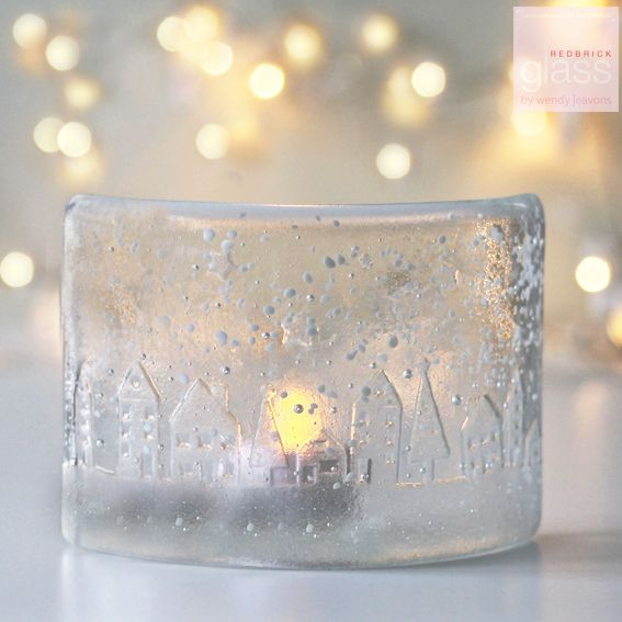 This beautiful curved peice of clear glass is embossed with little houses, trees and stars and has a sprinkling of glass snow. It looks magical when lit with a tea light candle or simply placed by a window to catch the sun light. Your tea light curve will come beautifully packaged in white tissue and comes with a small square dish to place your tealight. If this is a gift which you would like sent direct to the recipient Wendy can write a little message on a gift tag. 19cm by 10cm.